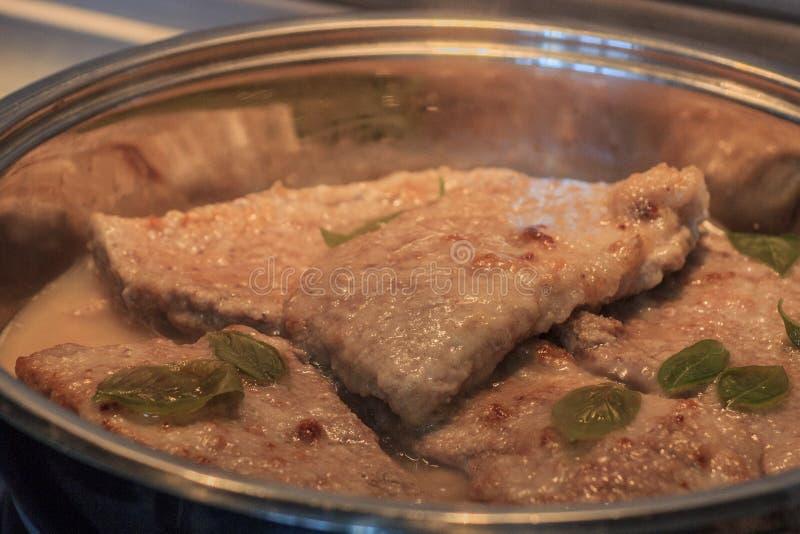 与紫花罗勒的自创肉 剁油煎了猪肉 手工制造鲜美食物 非常可口膳食 油煎肉平底锅 库存图片
