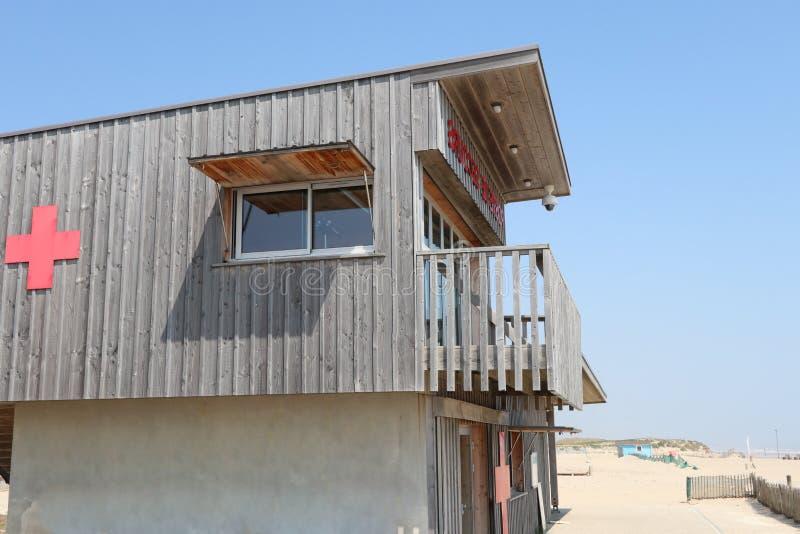 与红十字的一个救生员木小屋在沙子海洋海滩 库存照片