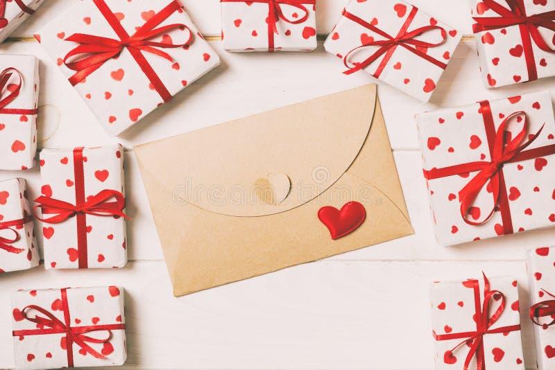 与红心和礼物盒的信封邮件在木葡萄酒被定调子的背景 情人节卡片、爱或者婚礼问候 库存图片