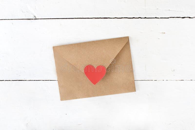与红心的情书信封在白色木背景 免版税图库摄影