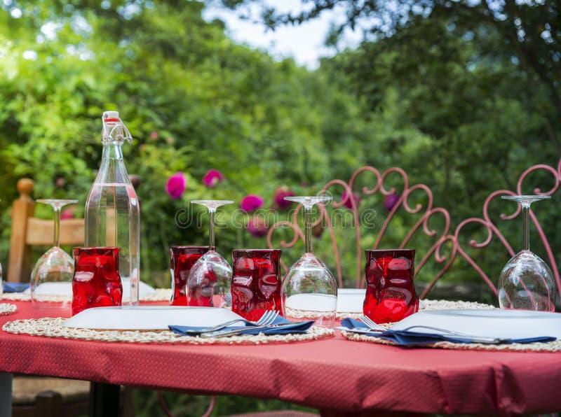与红潮玻璃的室外招待会桌 库存照片
