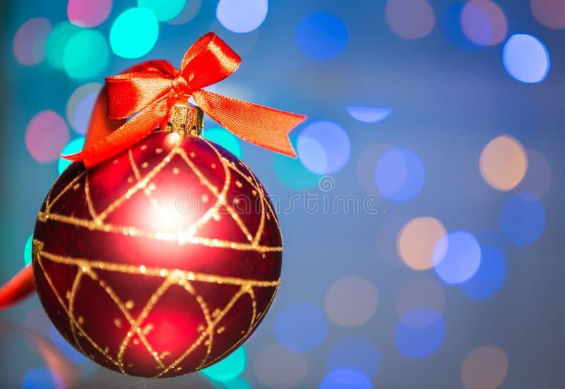 与红色丝带和美丽的Bokeh的圣诞节装饰 图库摄影