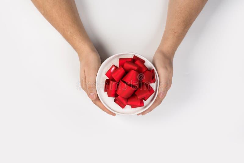 与红色丝带弓的小礼物在白色背景的人手上 库存图片