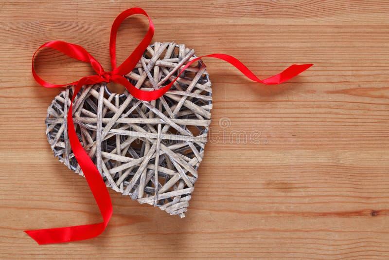 与红色丝带的心形的柳条装饰。 免版税库存照片