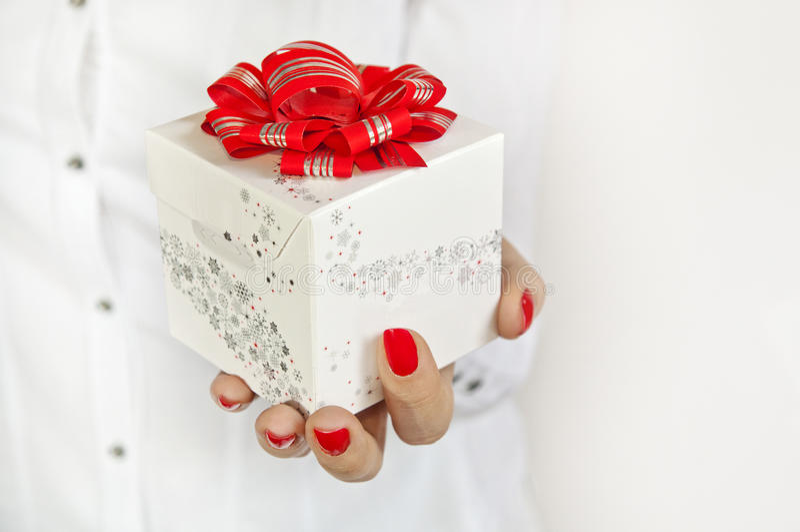 与红色丝带的白色礼物在妇女的手上 免版税库存照片