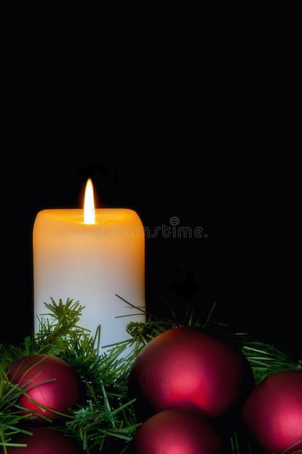 与红色中看不中用的物品的圣诞节蜡烛在黑色 免版税图库摄影