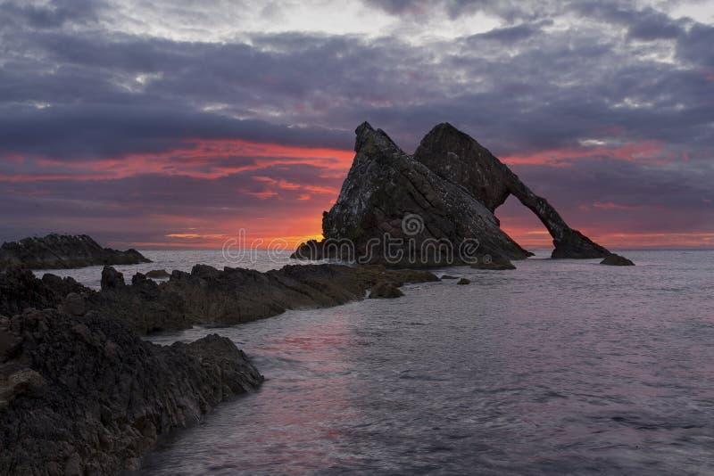 与红色云彩的日出在弓在Portknockie附近的无意识而不停地拨弄岩石 库存图片