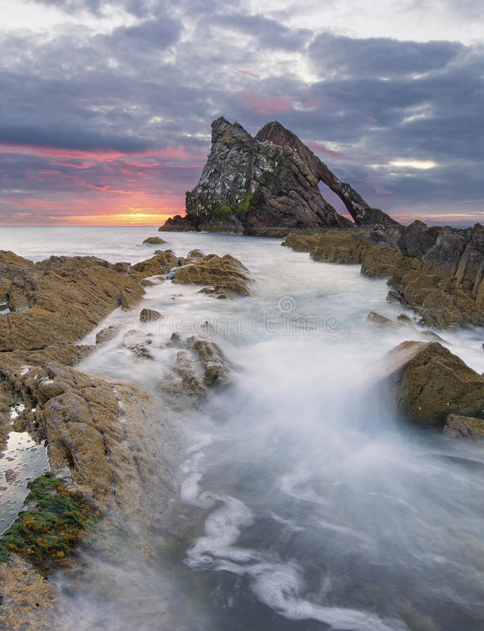 与红色云彩的日出在弓在Portknockie附近的无意识而不停地拨弄岩石 库存照片