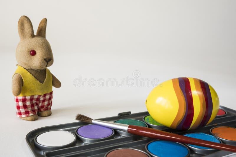 与红色刷子的绘的复活节彩蛋 黄色复活节彩蛋和填充动物玩偶在白色背景 文本的空间 免版税图库摄影