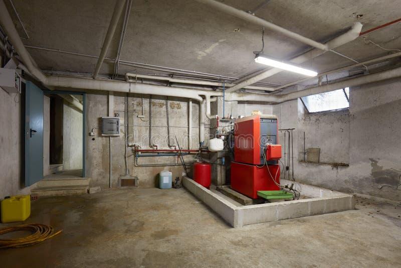 与红色加热的锅炉的地下室在老房子内部 免版税图库摄影