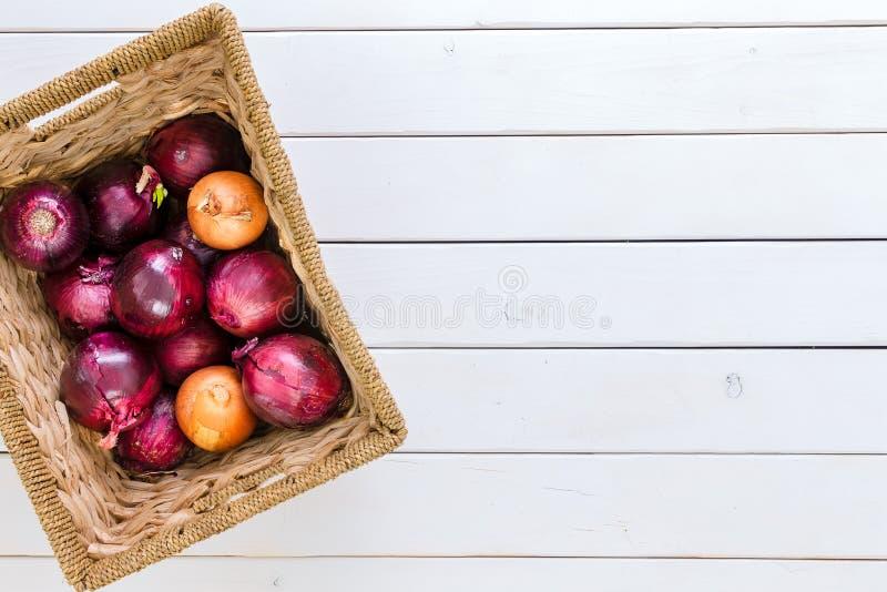 与红色和棕色葱的混合的土气篮子 免版税图库摄影