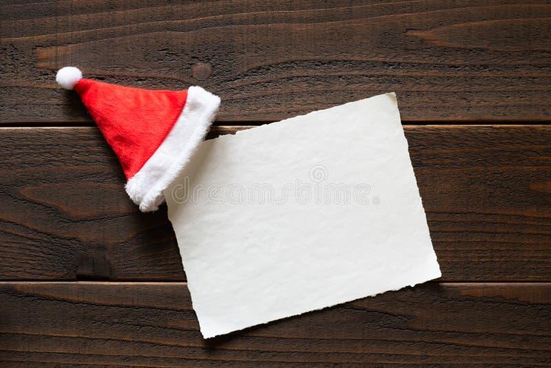 与红色和白色圣诞老人项目帽子的圣诞节假日纸牌党在黑暗,土气木表上的邀请或贺卡的 免版税库存图片