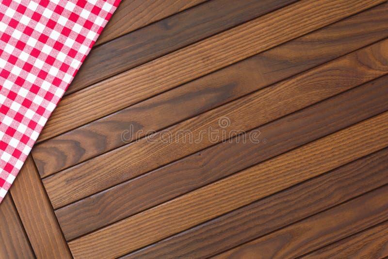 与红色和白色方格的桌布的木背景 库存照片