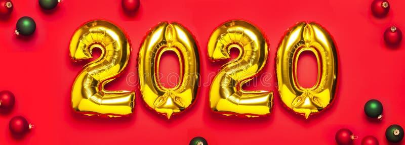 与红色和绿色圣诞节球的2020个可膨胀的金黄数字在红色背景 新年冬天装饰,假日标志, 图库摄影