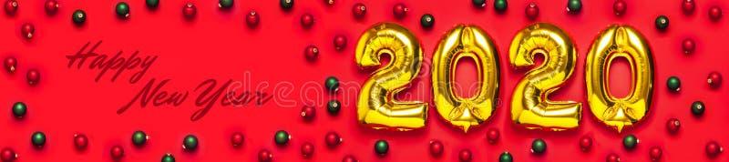 与红色和绿色圣诞节球的2020个可膨胀的金黄数字在红色背景 新年冬天装饰,假日标志, 库存照片