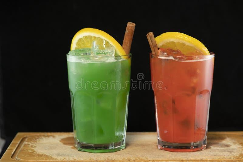 与红色和绿色汁液、酒精和石灰楔子的红色和绿色鸡尾酒 免版税图库摄影
