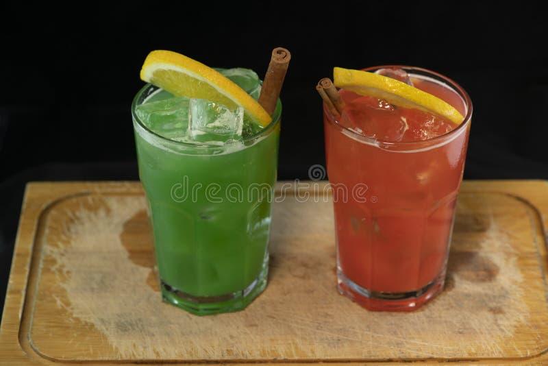 与红色和绿色汁液、酒精和石灰楔子的红色和绿色鸡尾酒 图库摄影