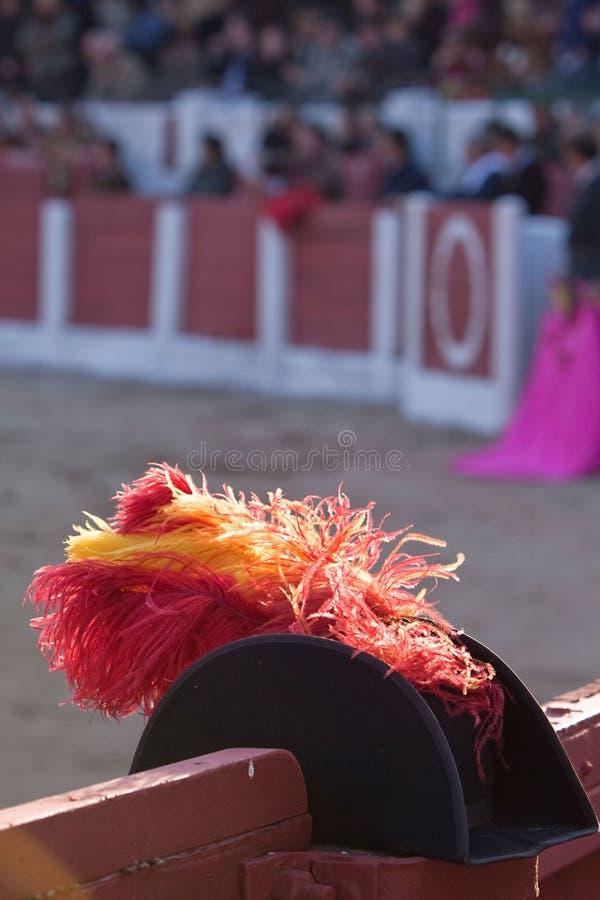 与红色和黄色羽毛的帽子alguacilillo在斗牛的burladero,西班牙 库存照片