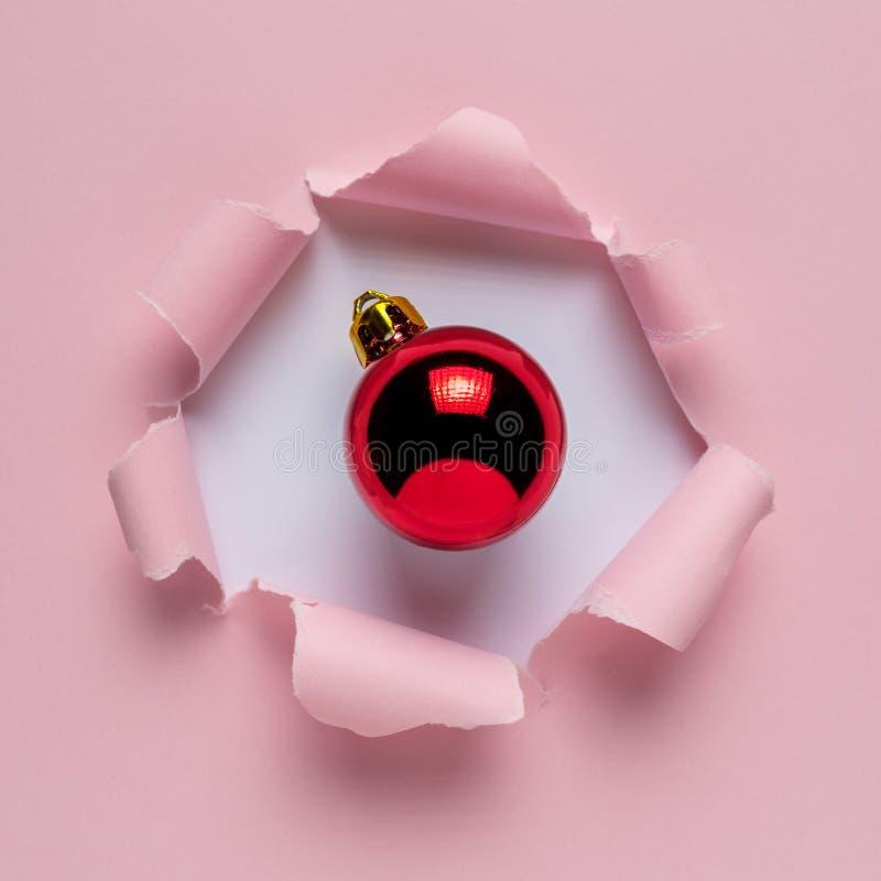 与红色圣诞节中看不中用的物品的生动的桃红色被剥去的纸 库存照片