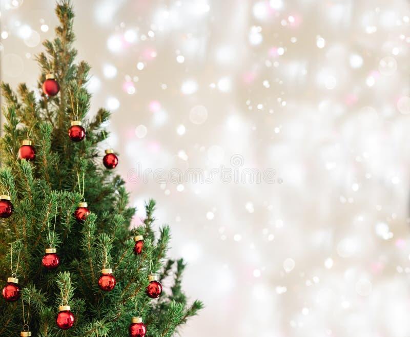 与红色圣诞装饰的圣诞树在与雪的假日背景,弄脏了,发火花 免版税库存照片