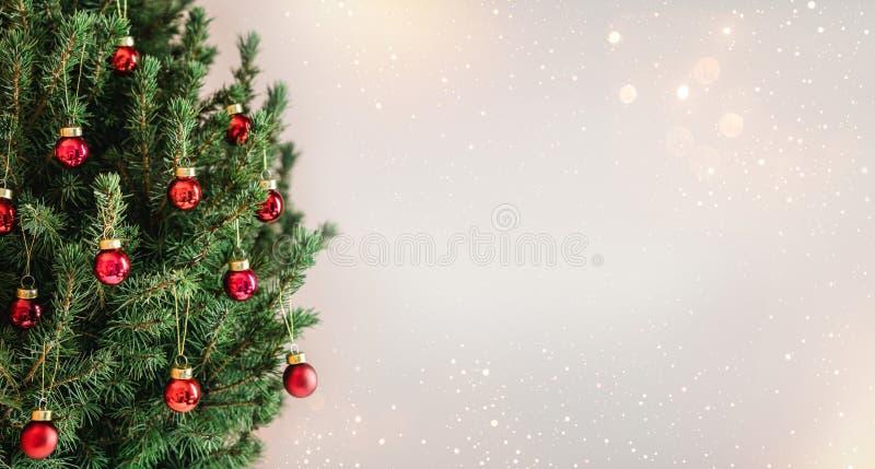 与红色圣诞装饰的圣诞树在与雪的假日背景,弄脏了,发火花 库存照片