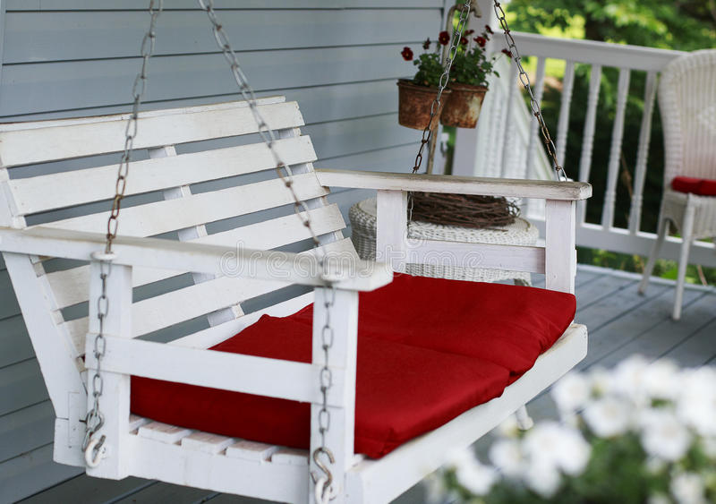 与红色坐垫的白色门廊摇摆 库存照片