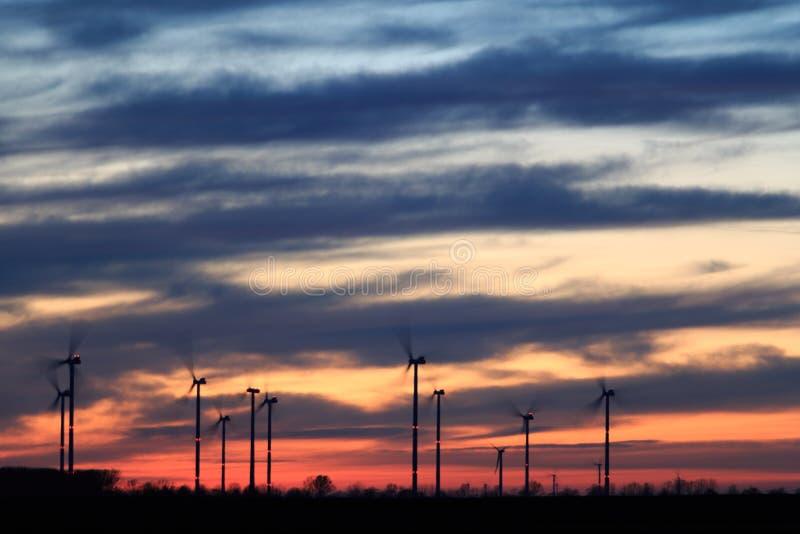 与红色天际和风力能量的日落风景 免版税图库摄影