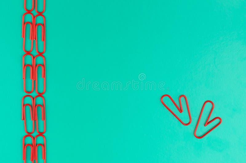 与红色夹子的绿色背景 两个红色纸夹形式心脏 免版税库存照片