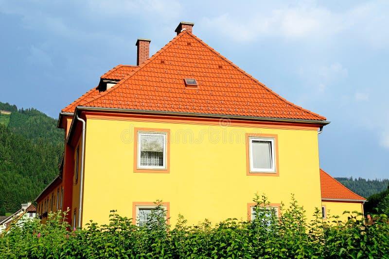 与红色屋顶的黄色huse在奥地利 免版税库存照片