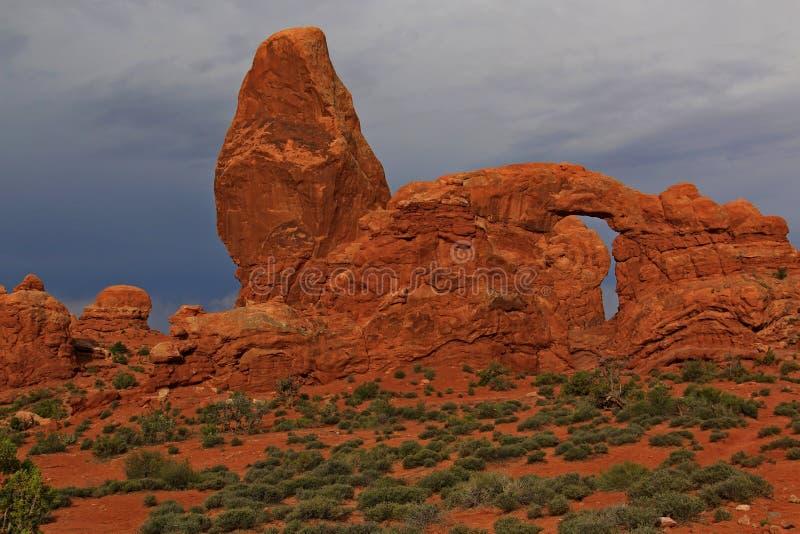 与红色岩石曲拱的灰色威胁的sky's对比 库存图片