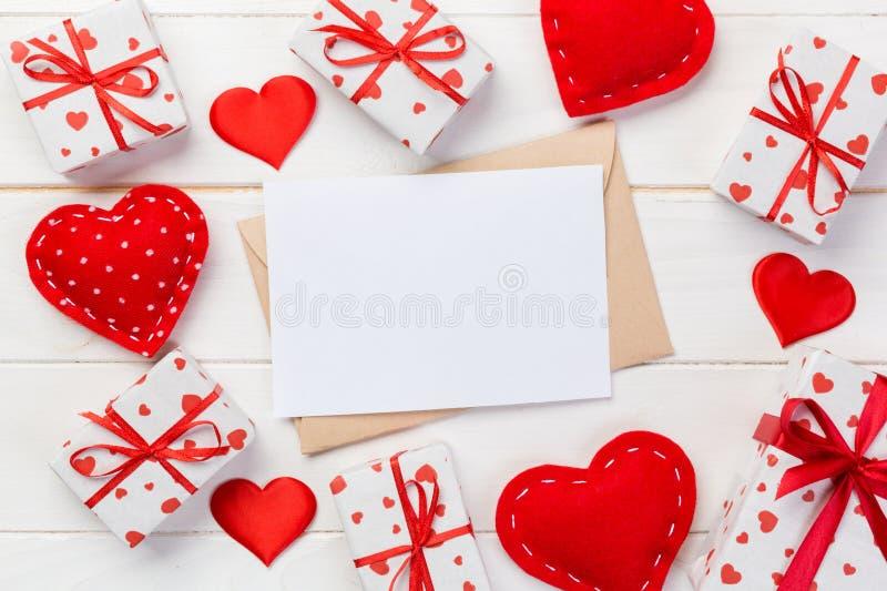 与红色心脏和礼物盒的信封邮件在白色木背景 情人节卡片、爱或者婚礼问候概念 免版税图库摄影