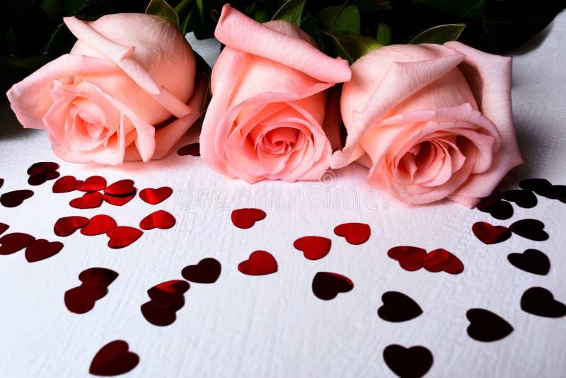 与红色心脏形状pailettes的三朵桃红色玫瑰 库存图片