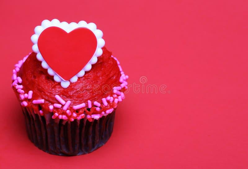与红色心脏的巧克力杯形蛋糕在上面,在红色背景 免版税库存照片