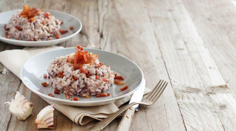 与红色拉迪基奥和酥脆烟肉斑点的意大利煨饭 免版税库存照片