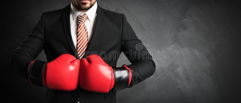 与红色拳击手套的商人在黑板前面 库存图片