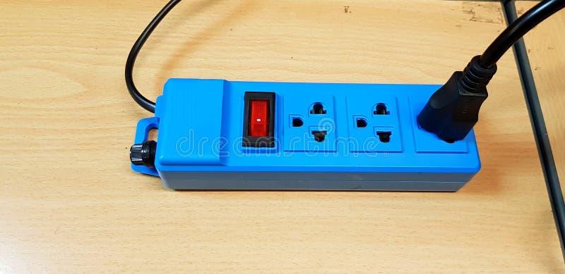 与红色按钮的蓝色AC出口或交换开关和黑人权力绳子缆绳连接 库存图片