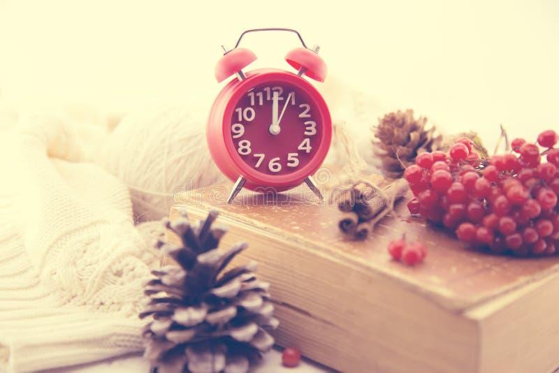 与红色时钟的冬天静物画作为新年、杉木锥体、花楸浆果和被编织的毛线衣的标志 节假日概念 免版税库存照片