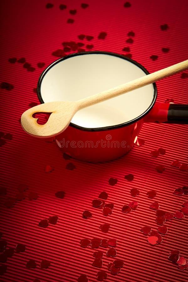 与红色有肋骨纸的情人节背景与红色平底深锅和木匙子恋人的 库存图片