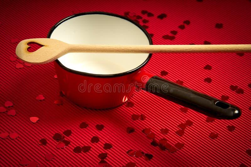 与红色有肋骨纸的情人节背景与红色平底深锅和木匙子恋人的 库存照片