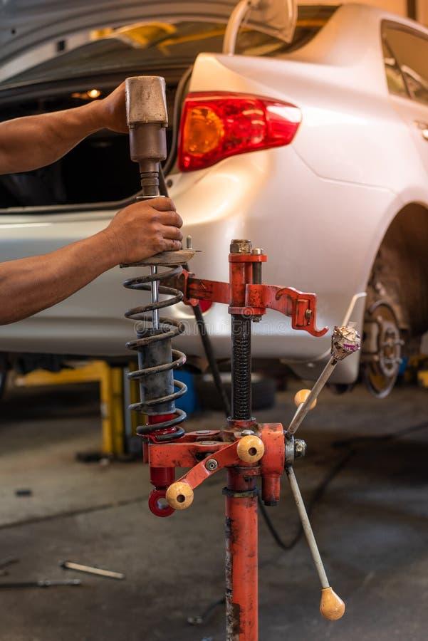 与红色机器的技工改变的汽车吸收体在自动修理服务 图库摄影