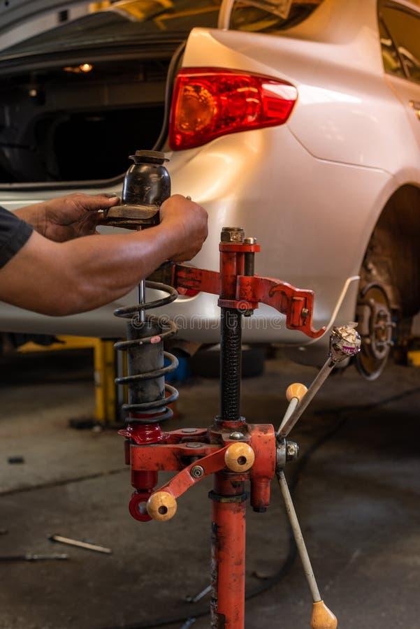 与红色机器的技工改变的汽车吸收体在自动修理服务 免版税库存照片