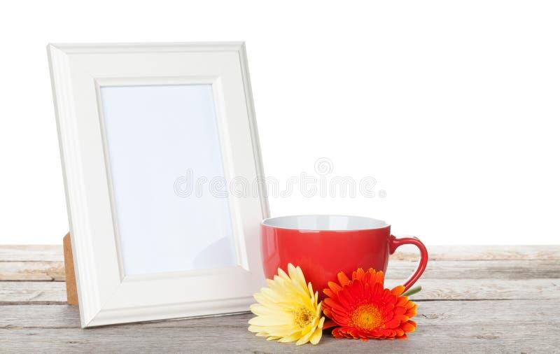 与红色杯子和twocolorful大丁草的照片框架开花 图库摄影