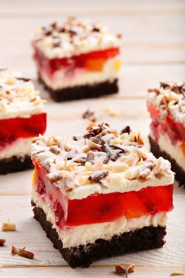 与红色果冻和巧克力的奶油色果子蛋糕剥落 库存照片