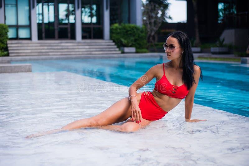 与红色比基尼泳装的戏弄的年轻微笑的妇女深色的秀丽在湿在的游泳池边大理石享用的夏天休息放置 免版税库存照片