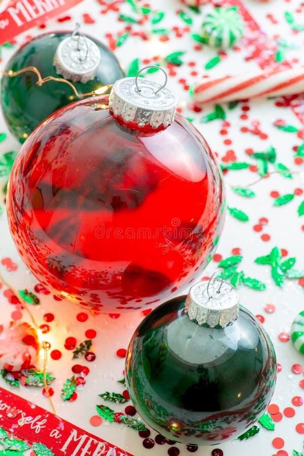 与红色流体充盈的圣诞节装饰品球的装饰和红色围拢的两个绿色被填装的装饰品球有你自己上午 免版税库存图片