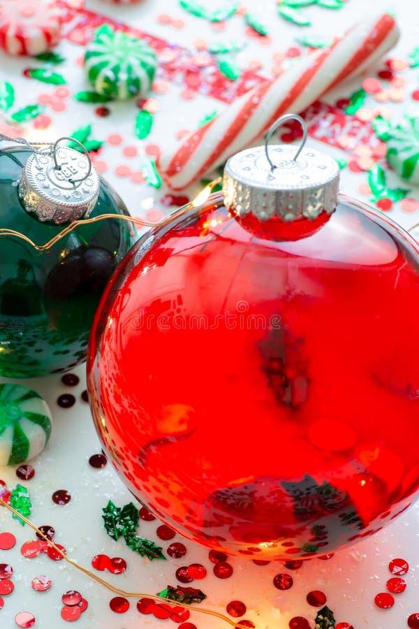 与红色流体充盈的圣诞节装饰品球的装饰和红色围拢的两个绿色被填装的装饰品球有你自己上午 免版税图库摄影
