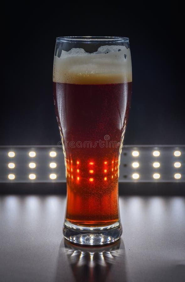 与红色液体的玻璃,玻璃用红宝石啤酒 免版税库存图片