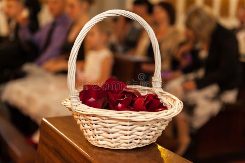 与红色玫瑰花瓣的木篮子 库存图片