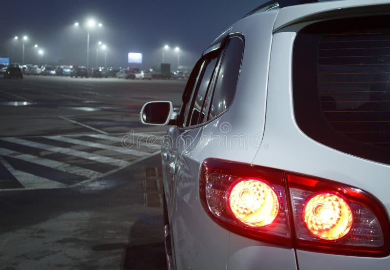 与红色的白色SUV在停车处停止 免版税库存图片