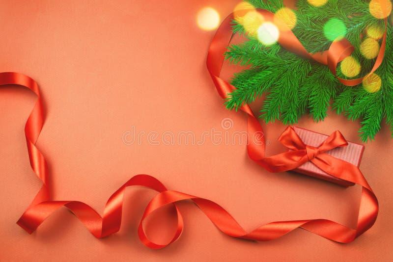 与红色礼物盒和红色丝带,圣诞树在红色背景的分支的平的位置和圣诞灯bokeh 免版税库存图片